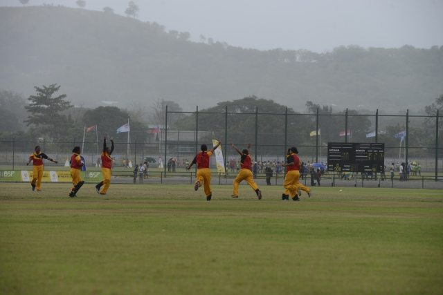 Pitch imperfect: Constant rain did not stop the cricket competition, here PNG players celebrate taking a Samoa wicket. Photo by Olga Fontanellaz.