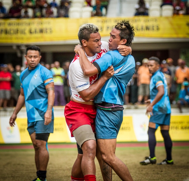 Guam in arm: Players from Tahiti and Guam grapple in rugby 7s. Photo by Dave Buller.