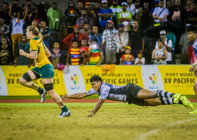 Ankle flap: A Fijian player swipes unsuccessfully at an escaping Australian in the women's rugby 7s final. Photo by Dave Buller.